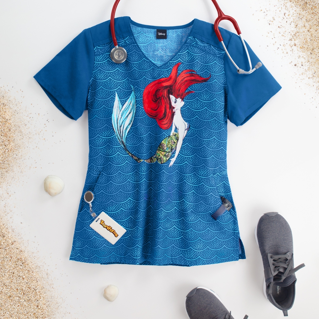 Make the Cherokee Tooniforms Disney Mermaid Life V-Neck Contrast Print Scrub Top part of your world. This top has 2 side entry pockets, side slits, royal contrast sleeves and is made up of 100% cotton.