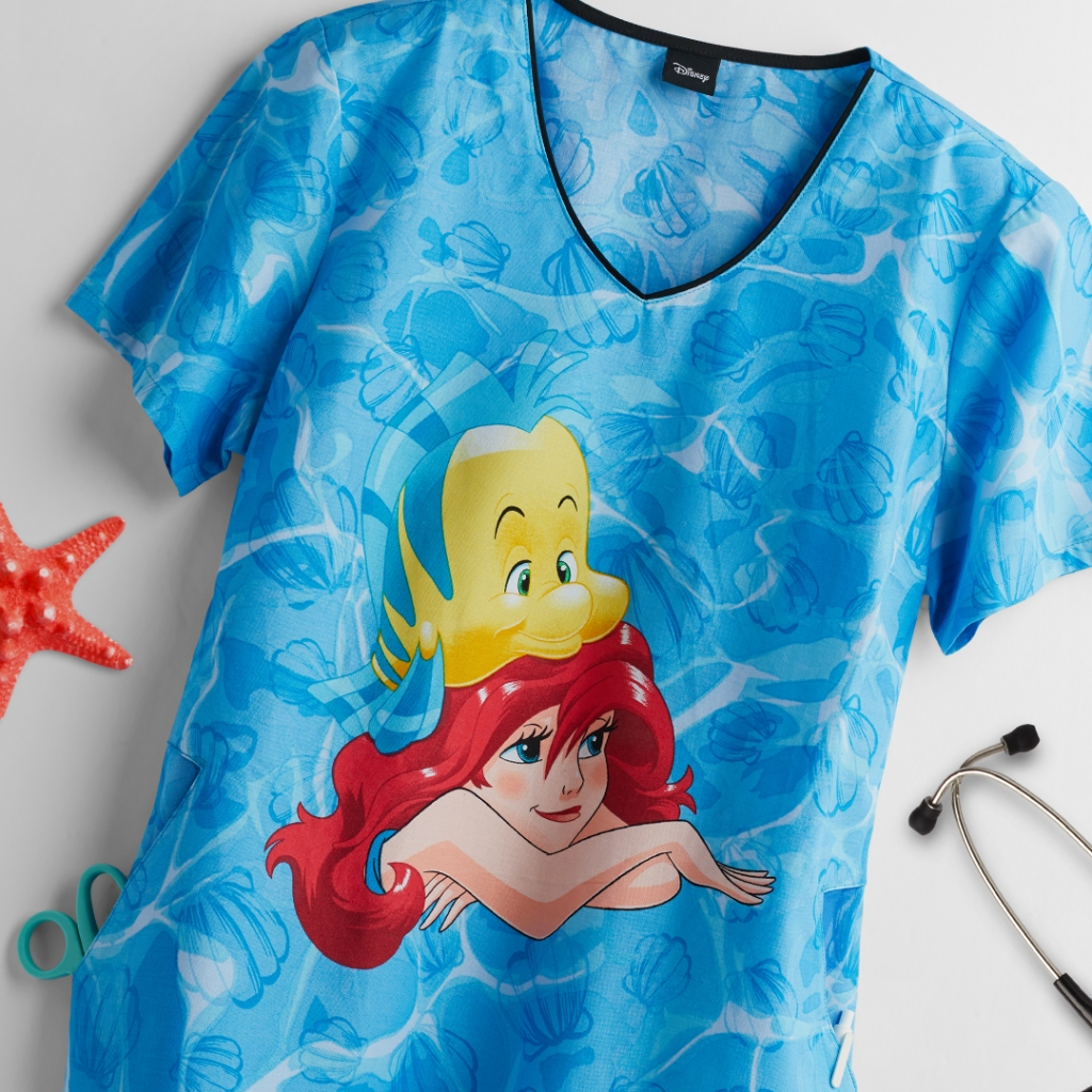 The Cherokee Tooniforms Disney Ariel and Flounder V-neck Print Scrub Top features Ariel and Flounder from The Little Mermaid. Made of 100% cotton, this top has two side pockets, bust darts, back darts and side slits.