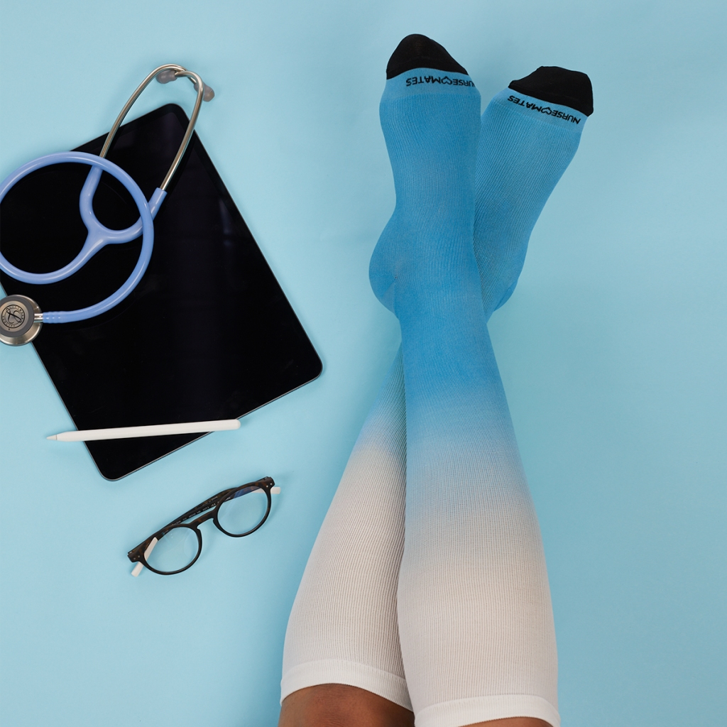 Nurse Mates Ombre Marina Blue Compression Socks. These cute socks feature 12-14 mmHg graduated compression with a comfort welt top band, heel and toe pockets. The fabric content is 87/13 nylon/spandex.