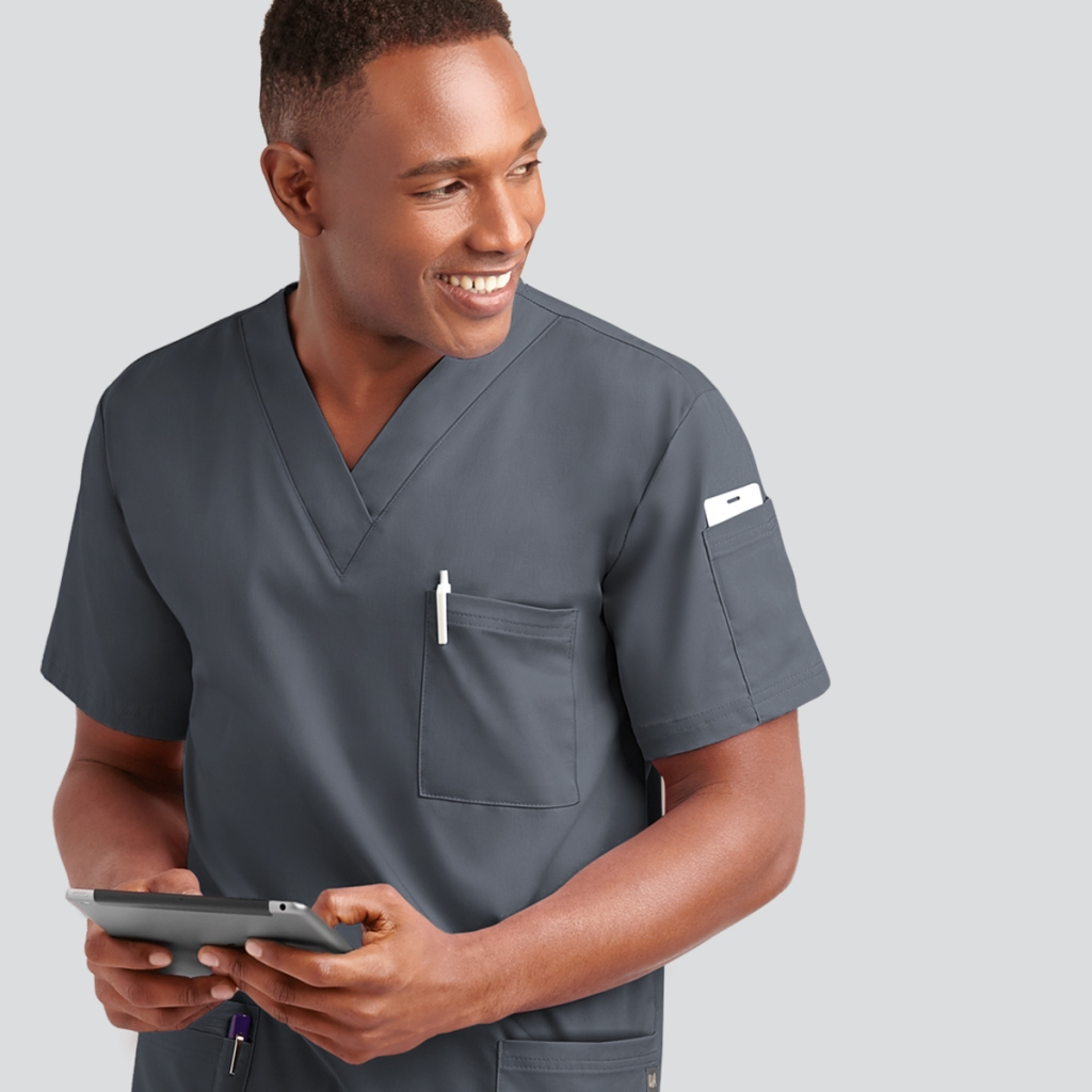 man in pewter scrubs on tablet